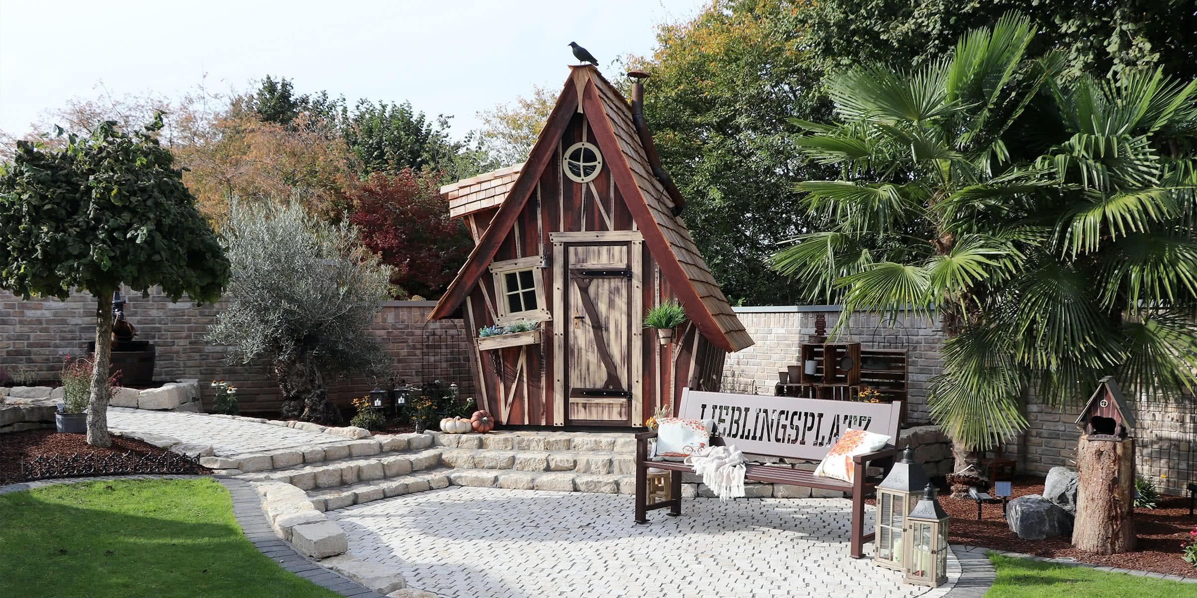 Kleine Häuschen im Garten mit gelaserter Bank daneben